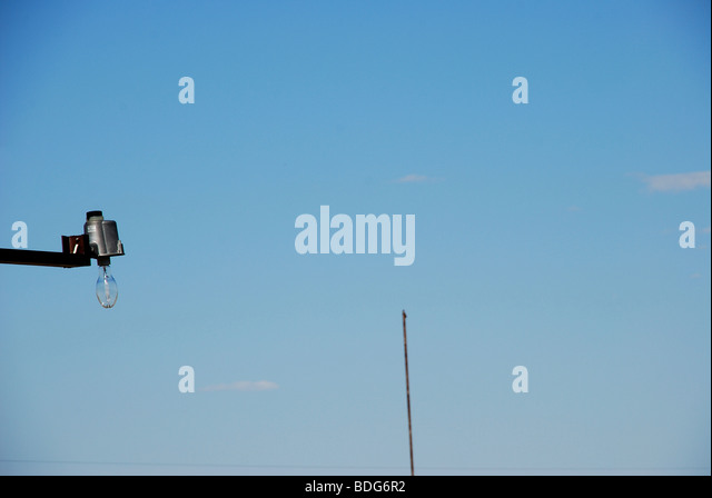 Light bulb against clear blue sky with pole in background - Stock Image
