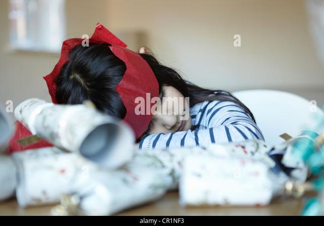 Girl in paper crown sleeping at desk - Stock Image