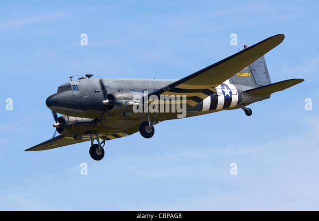 Douglas C-47A Skytrain, military version of the DC-3 Dakota,in USAAF D-Day markings on approach for landing At RAF - Stock Image