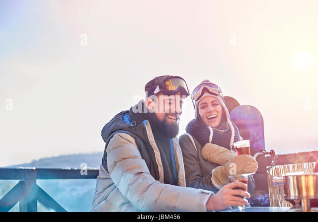 Snowboarder couple laughing, drinking cocktails on sunny balcony apres-ski - Stock-Bilder