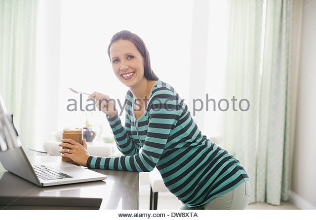 Portrait of pregnant woman eating peanut butter - Stock Image