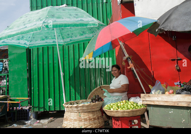 Managua Nicaragua Mercado Oriental flea market marketplace shopping vendor merchant Hispanic woman job produce stand - Stock Image