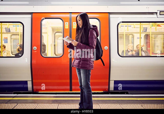A young Japanese woman at a tube station in London - Stock Image