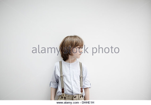 Boy standing against white wall - Stock Image