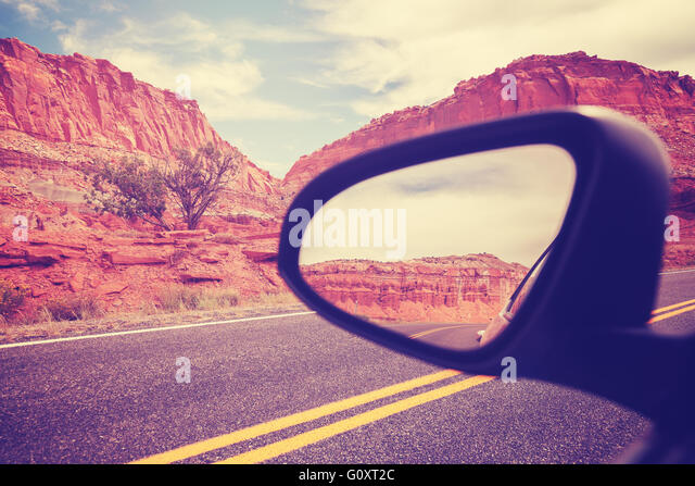 Vintage stylized car wing mirror, focus on mountains, travel concept. - Stock Image