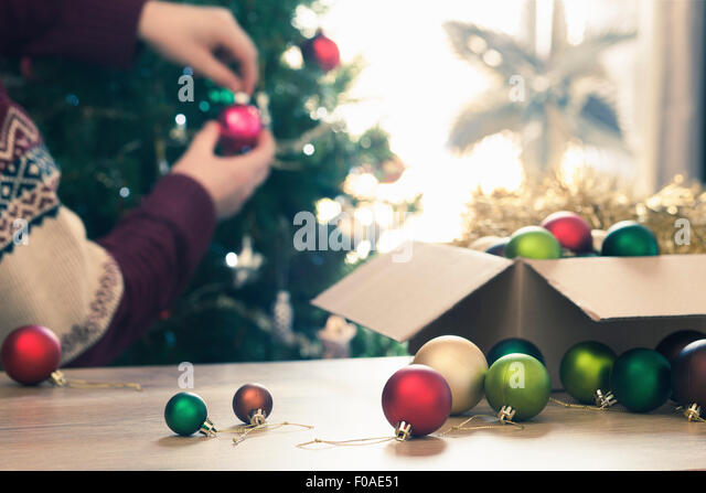 Person decorating christmas tree - Stock Image