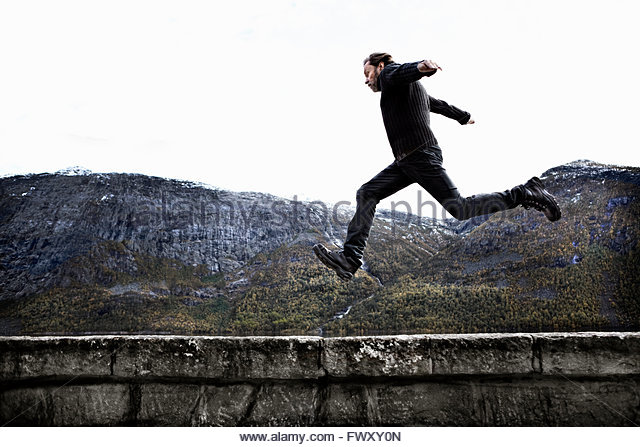 Norway, Odda, Man jumping over stone wall - Stock-Bilder