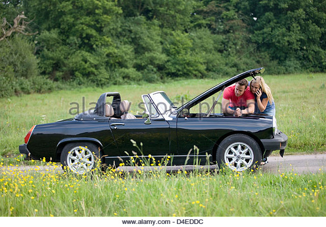 A young couple standing next to their broken down sports car speaking on a mobile phone - Stock Image