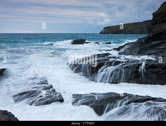 Fierce Atlantic waves crash over the dark slate cliffs of Trebarwith Strand, Cornwall, England. Summer (July) 2011 - Stock Image