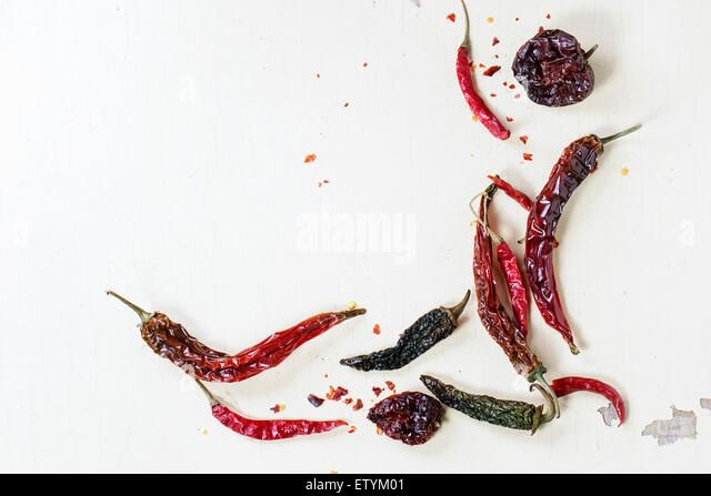 Assortment of dryed red hot chili peppers over white wooden background - Stock Image
