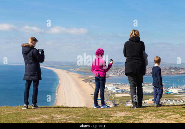 A German family are taking photos and enjoying the view overlooking Portland harbour and Chesil Beach on a sunny - Stock-Bilder