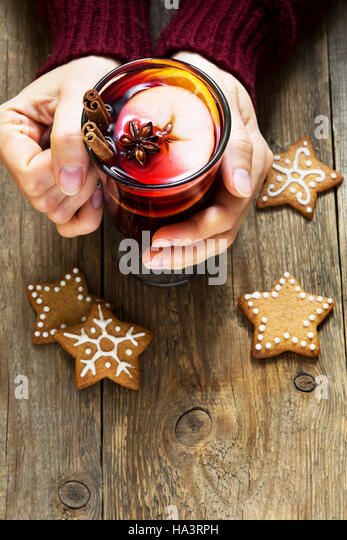 Christmas hot drink - mulled wine in female hands with cinnamon stick, star anise and festive Christmas gingerbread - Stock Image