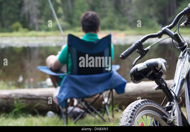 A teenage boy fishing by the lakeside in his camp chair. Focus on the bike. - Stock Image