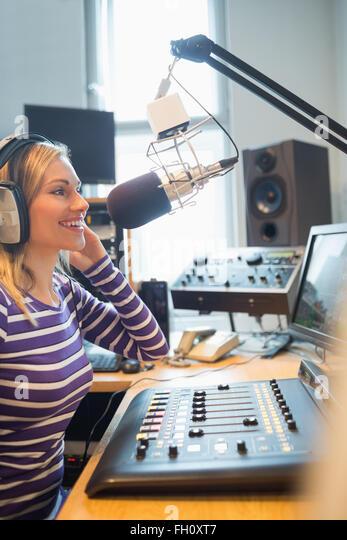 Happy female radio host broadcasting through microphone - Stock-Bilder