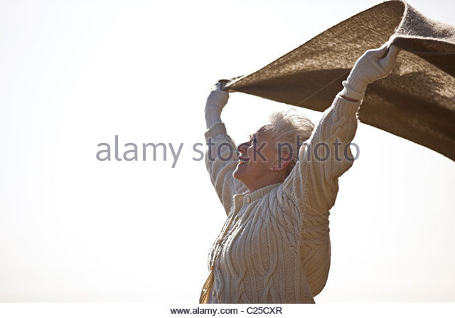 A senior woman holding a blanket into the wind - Stock Image