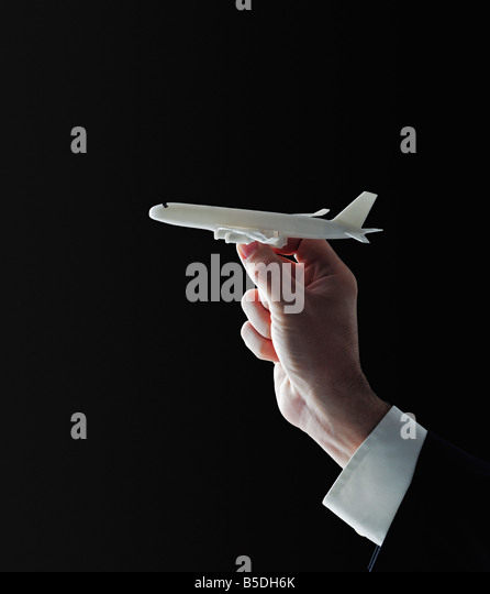 Model Aeroplane in the Hand of a Businessman Against Black Background - Stock Image