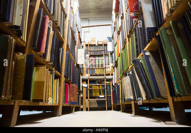 Very old library in a bad condition. Books on shelves. Ladder at the back of the bookshelves. - Stock Image