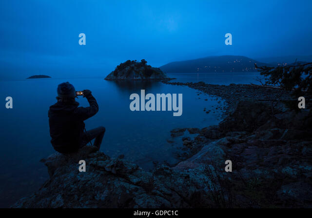 Silhouette of man by Pacific Ocean, Whytecliff Park, West Vancouver, British Columbia, Canada - Stock Image