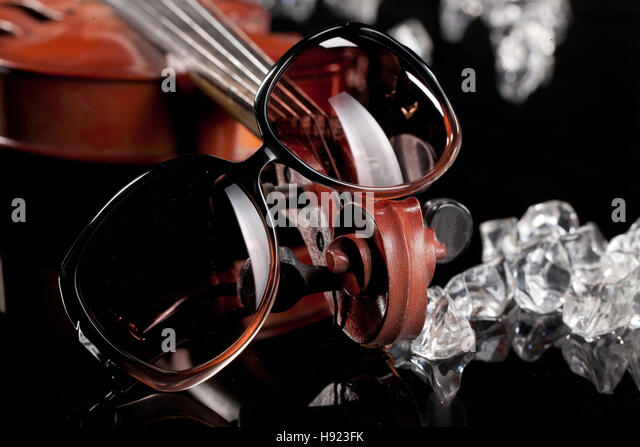Sunglasses, violin, pieces of ice on a glass background - Stock Image