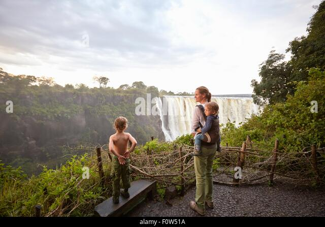 Mother and sons admiring view, Victoria Falls, Livingstone, Zimbabwe - Stock Image
