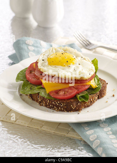 A breakfast sandwich stack with toast, arugula, tomato, cheese, ham and an egg on a white plate - Stock Image