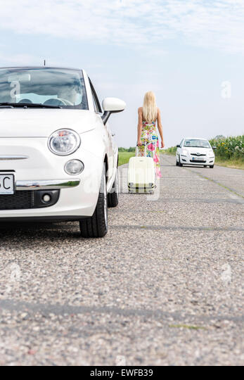 Rear view of woman with luggage leaving broken down car on country road - Stock-Bilder