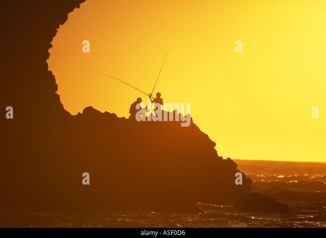 Fishermen on rocks at sunset Piha New Zealand - Stock Image