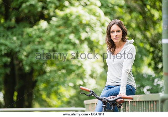 Portrait of mid adult woman sitting on fence in park - Stock Image