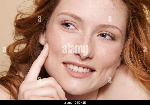Studio shot of young woman with curly red hair, hand on chin pointing - Stock Image