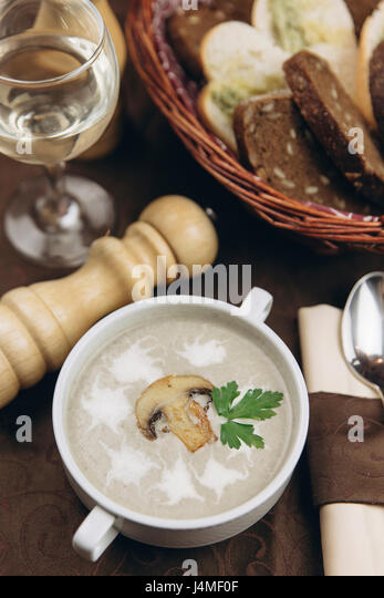 Mushroom floating in cup of soup - Stock-Bilder