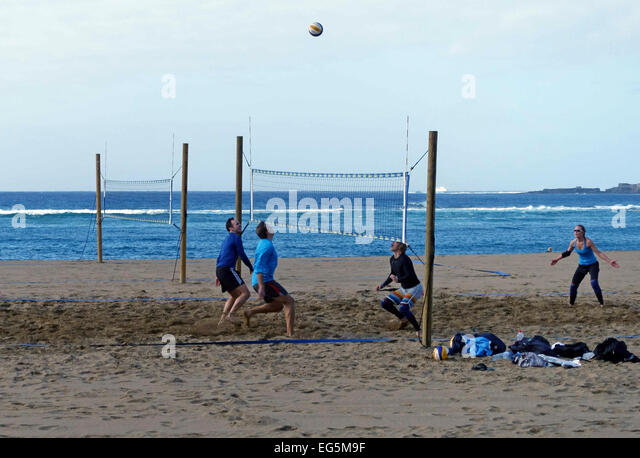 Holidaymakers play beach volleyball in Las Palmas de Gran Canaria, Canary Islands - Stock Image