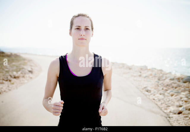 Woman in sports clothing  jogging on waterfront path - Stock Image
