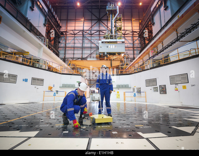 Engineers using sensors on pile cap in nuclear power station - Stock Image