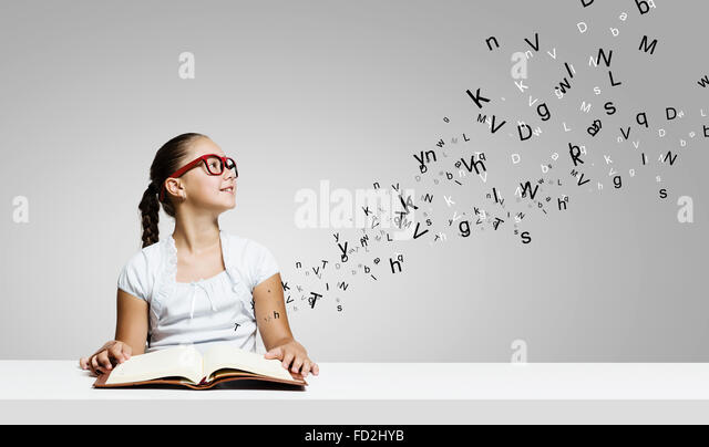 Cute girl of school age with book in hands - Stock Image