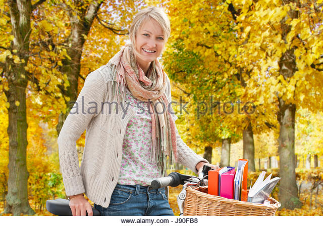 Portrait Of Female Student Riding Bicycle - Stock-Bilder
