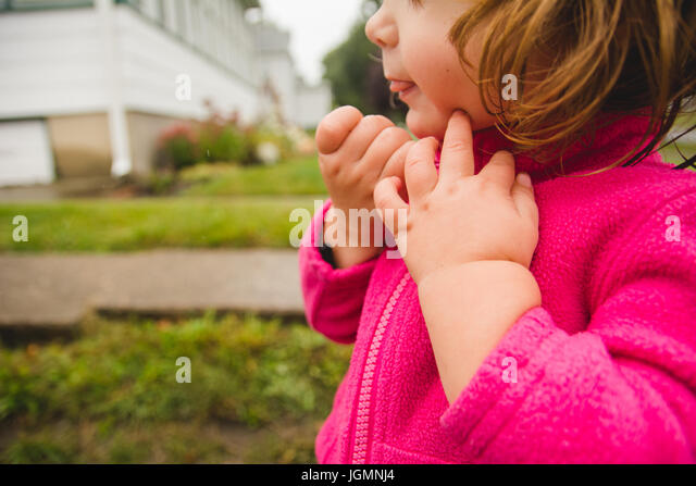 A toddler zipping her jacket hands only. - Stock Image
