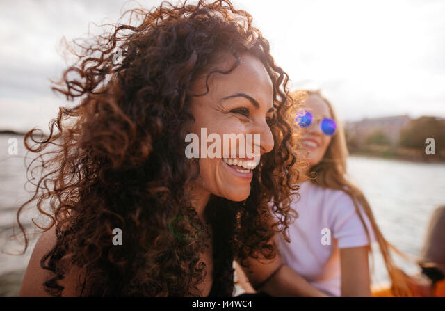 Close up shot of cheerful young woman outdoors with female friend in background. - Stock Image