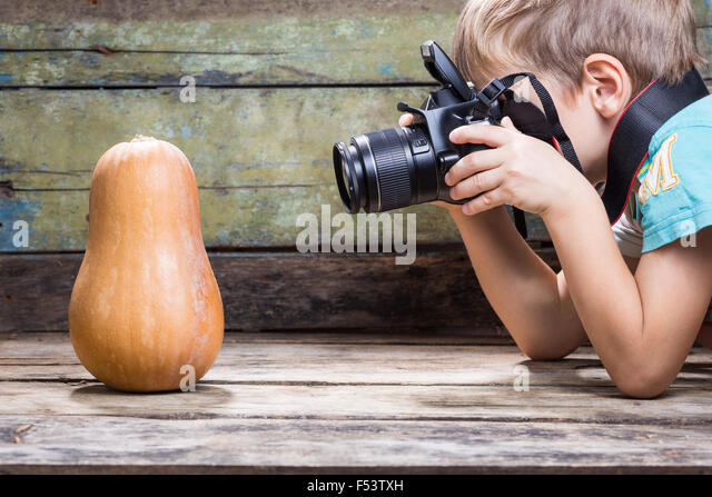 Funny fair boy use DSLR camera trying to take photo of ripe pumpkin on wooden background in studio. Photography - Stock Image