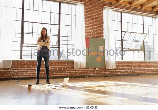 Portrait of young woman standing in empty office space, laptop on floor in front of her - Stock-Bilder