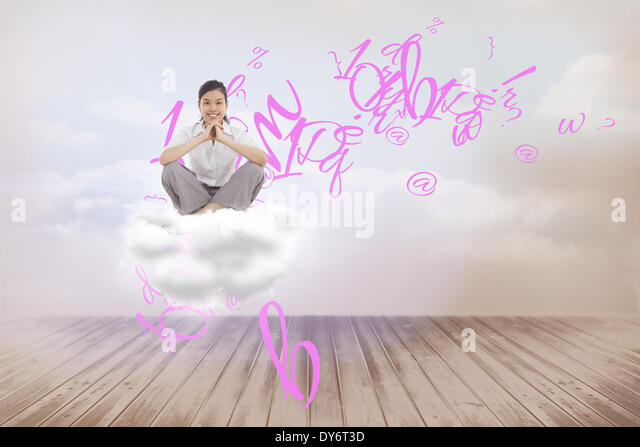 Composite image of businesswoman sitting cross legged with hands together - Stock Image
