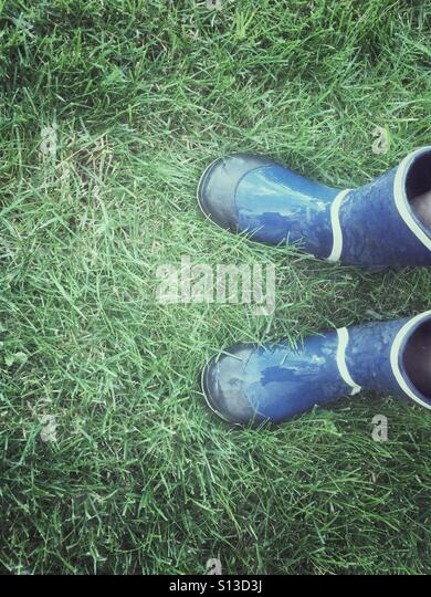 Blue boots on wet grass. - Stock Image