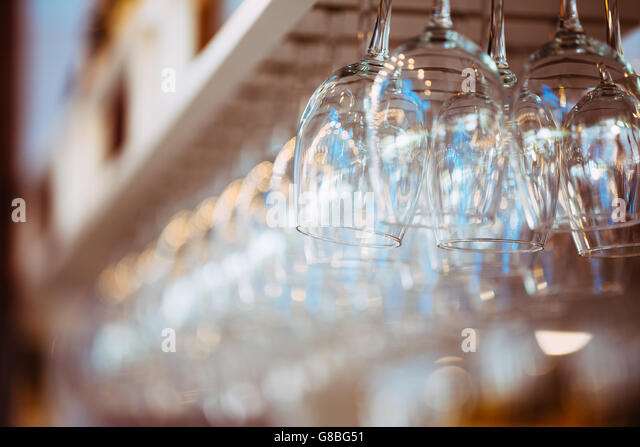Glasses hanging over  bar rack. Glasses for wine above a bar rack - Stock Image