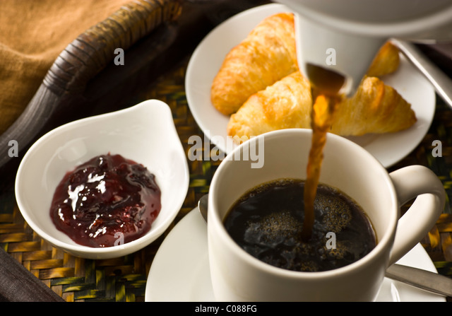 A tray with croissants, jam and a cup of hot black coffee being poured - Stock-Bilder