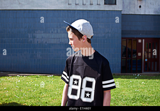 Portrait of boy wearing baseball cap looking away - Stock Image