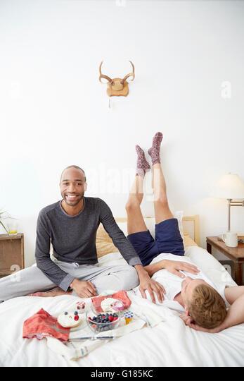 Homosexual couple on bed having breakfast - Stock-Bilder