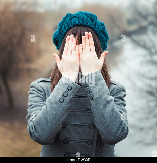 young pretty girl with hands over eyes outdoors - Stock Image