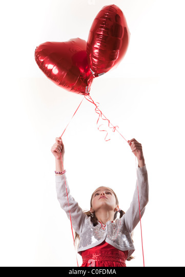 happy girl holding heart shaped balloons - Stock Image