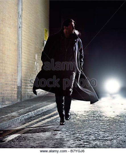 man in overcoat running down street at night - car lights behind - Stock Image