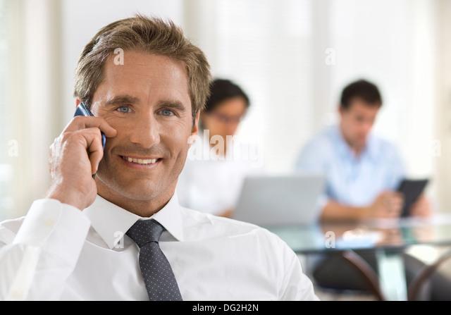 Male mobile phone office desk looking camera - Stock-Bilder