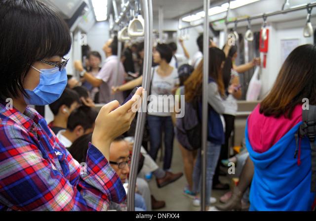Beijing China Dongsi Subway Station Line 5 6 public transportation train cabin Asian woman passenger rider smartphone - Stock Image